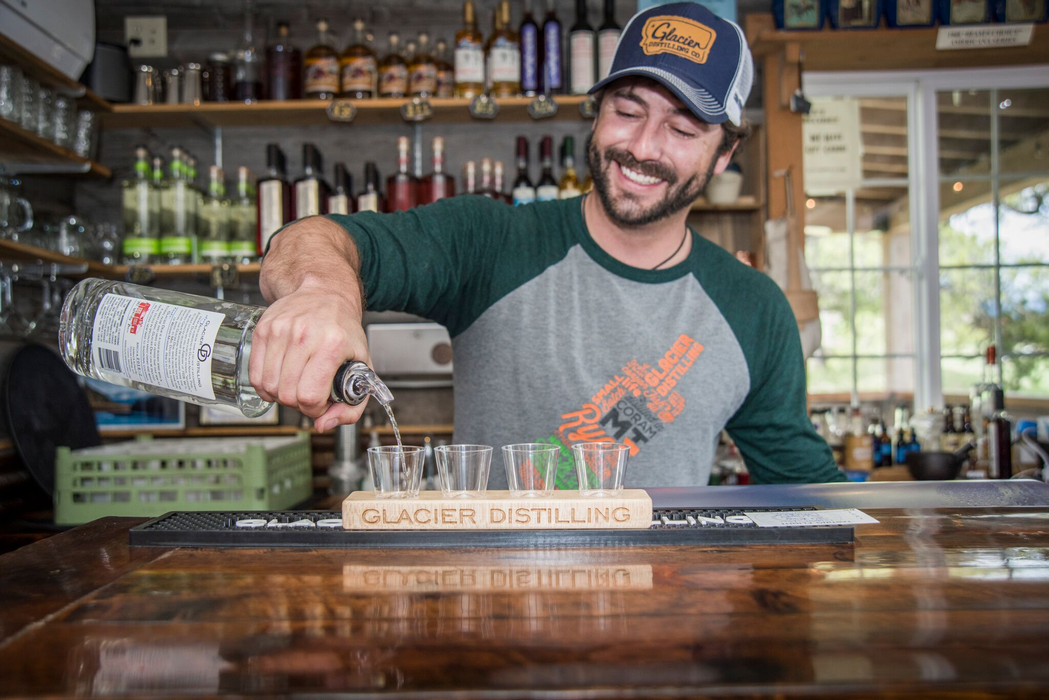 A bartender pours samples of fine spirits at Glacier Distilling in Corman, Montana.