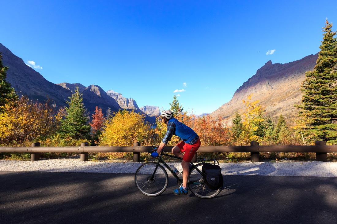 A cyclist takes in the fall view in Glacier National Park, Montana on the Going to the Sun Road.